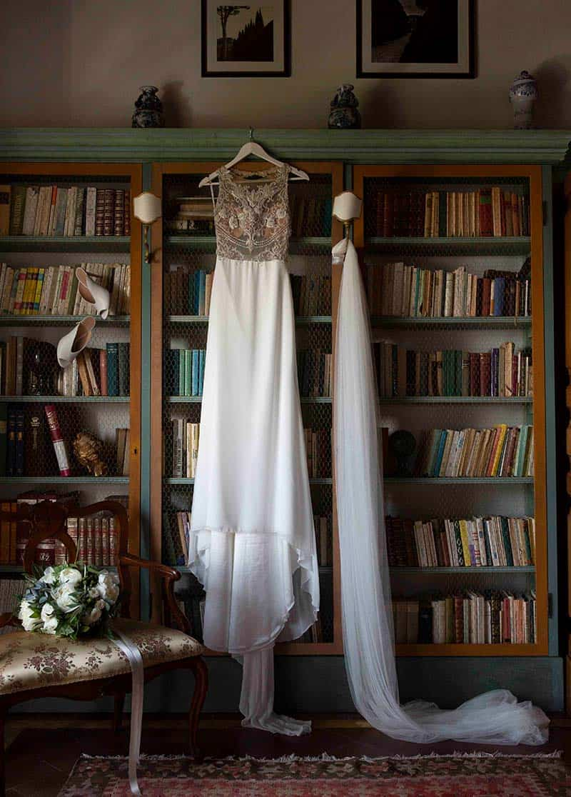 long white wedding dress hanging from a bookcase