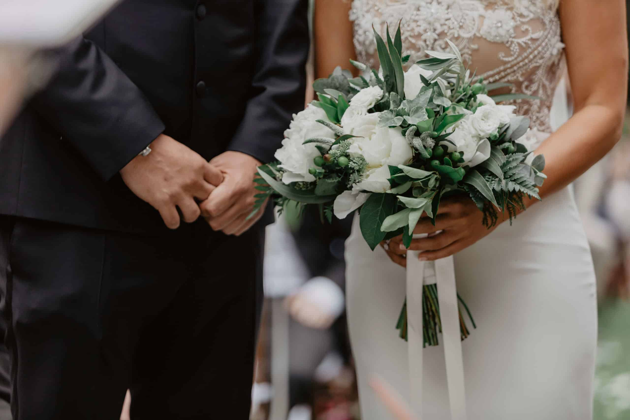 Newlyweds getting married, she has a bouquet of white roses in her hand