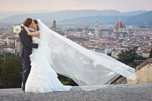 Bride and groom kissing each other on Piazzale Michelangelo, a terrace overlooking Florence. The veil of the bride flows in the wind.