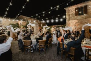 Wedding reception, the guests are seated during dinner and the bride and groom walk by the tables while all the guests waving all the napkins
