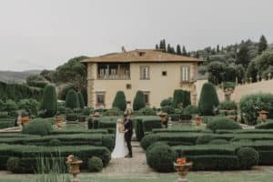 Bride and groom looking at each other in front of the amazing Tuscan villa called Villa Gamberaia