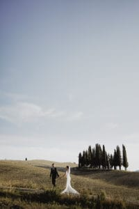 Bride and groom holding each other hands while walking in the Tuscan countryside.