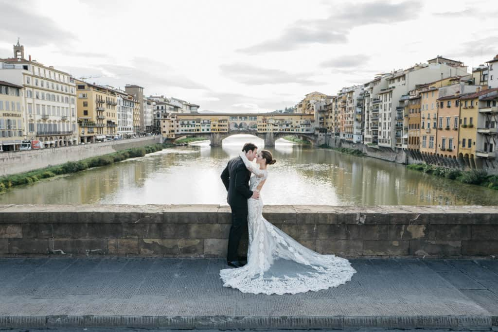 The groom and the bride kissing in front of Ponte Vecchio, one of the most famous monument in Florence