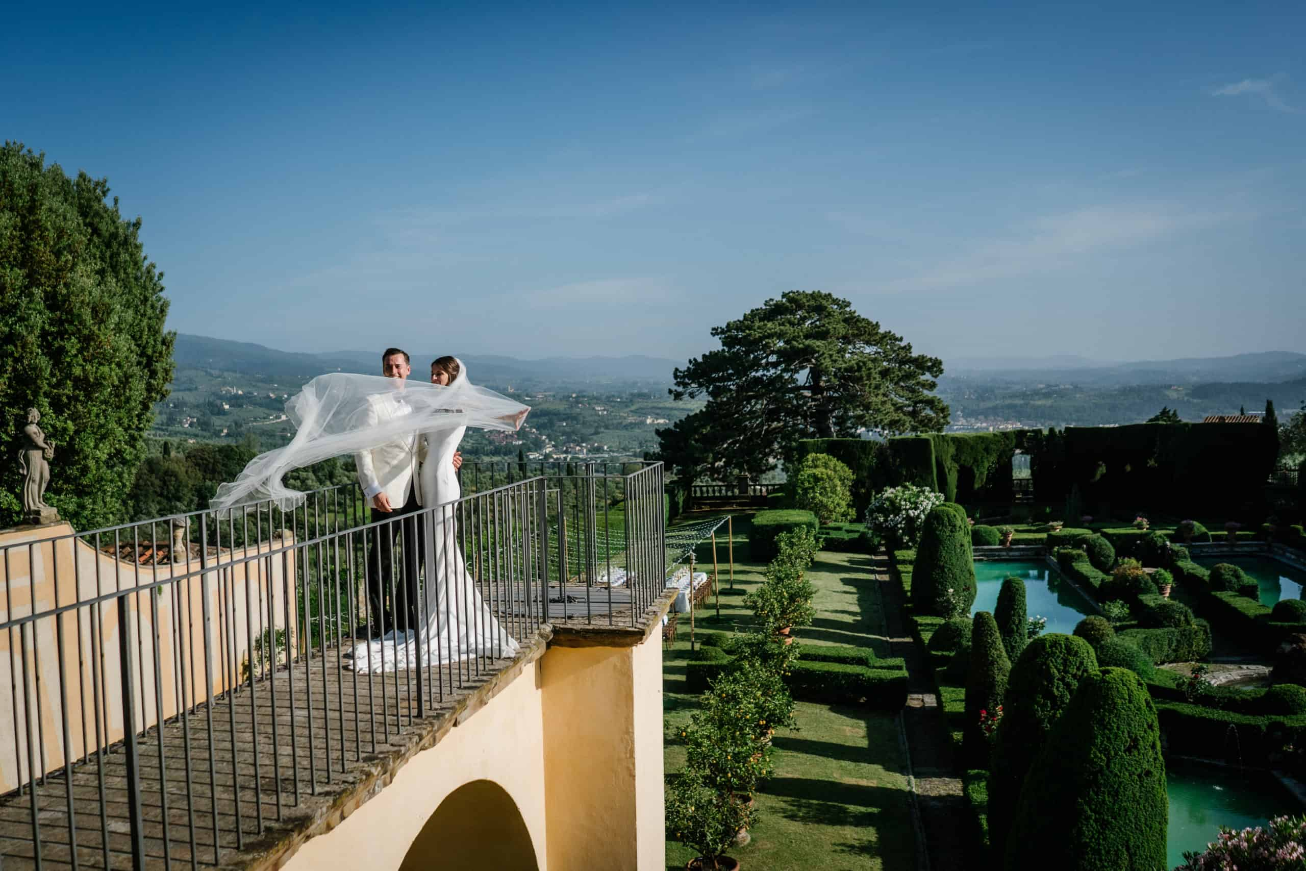 Bride and Groom look over the Tuscan landscape and villa grounds. The bride's veil flows in the sky.