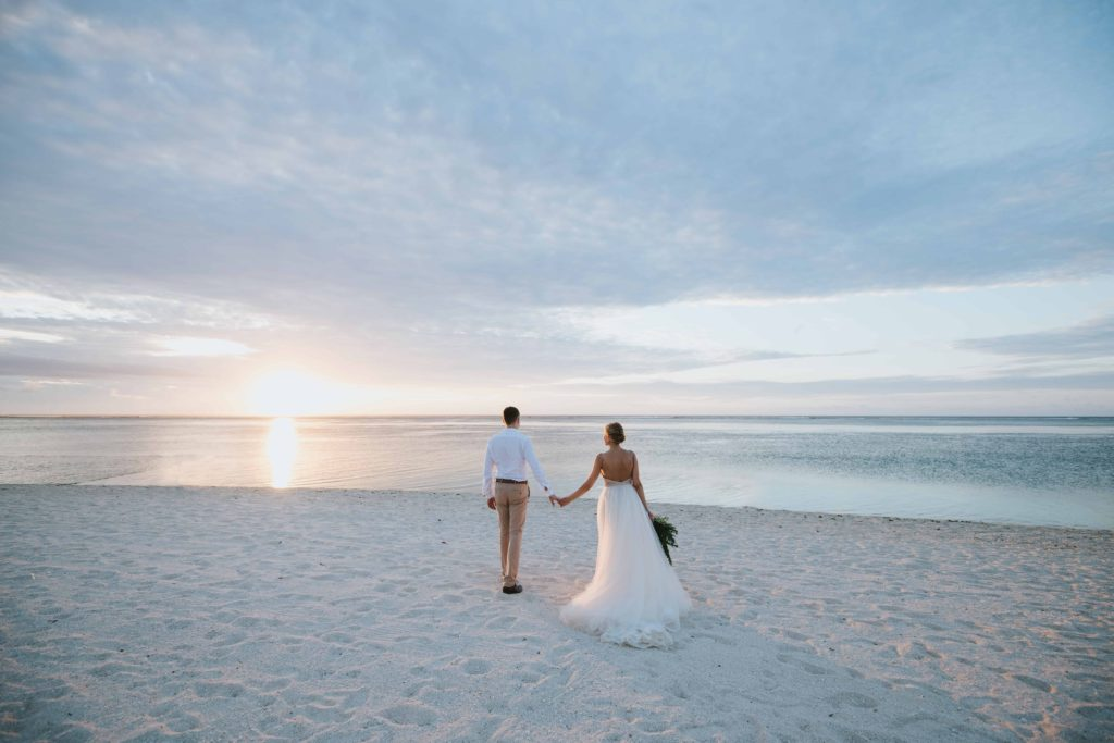 Bride and groom walk hand in hand at their beach wedding in Italy