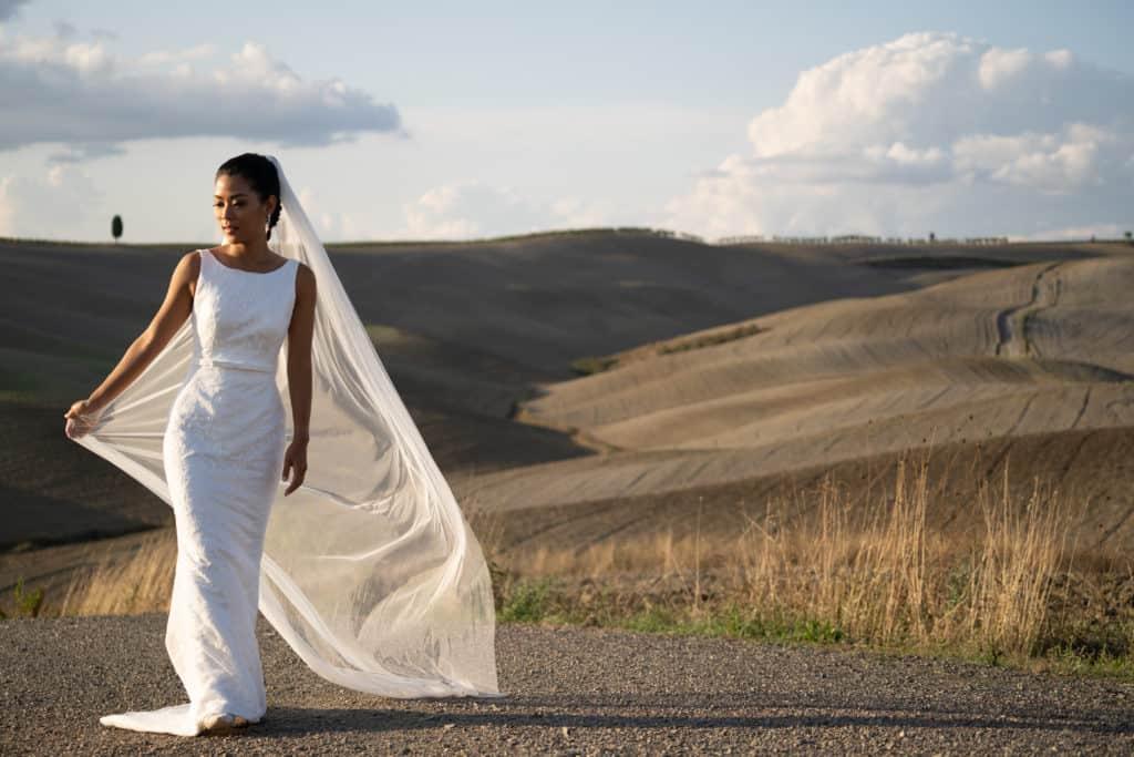 Bride waking through Tuscan vineyard