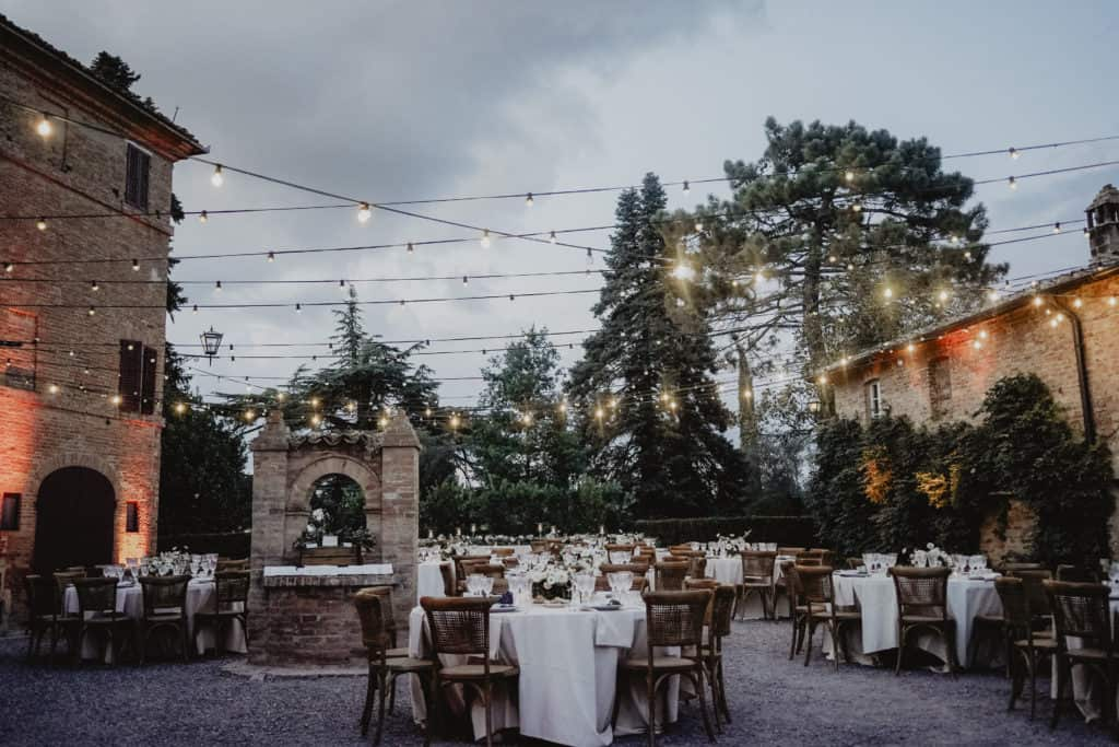Italian vineyard rustic chic wedding. The location is decorated with lights and the tables have with robe and chairs.