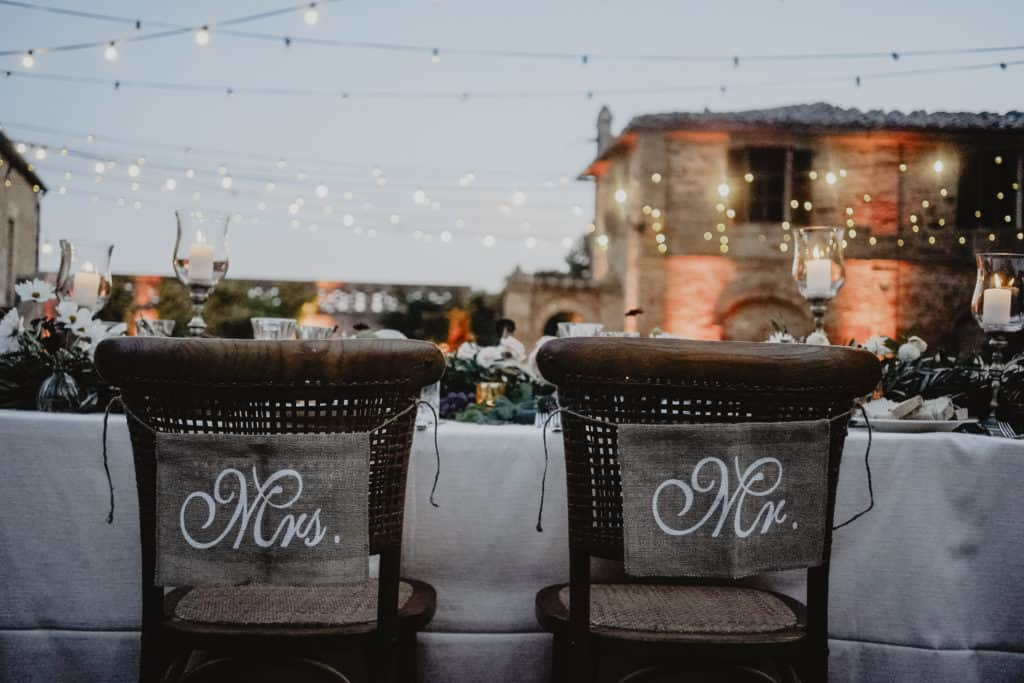 """Wedding chairs details. The newlyweds chairs are decorated with the sign """"Mrs"""" and """"Mr""""."""