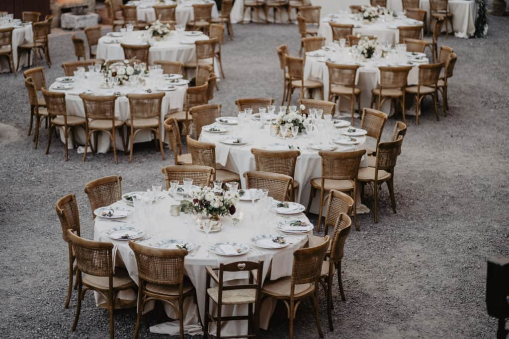 Rustic chic wedding round tables decorated with white robe and wooden chairs.