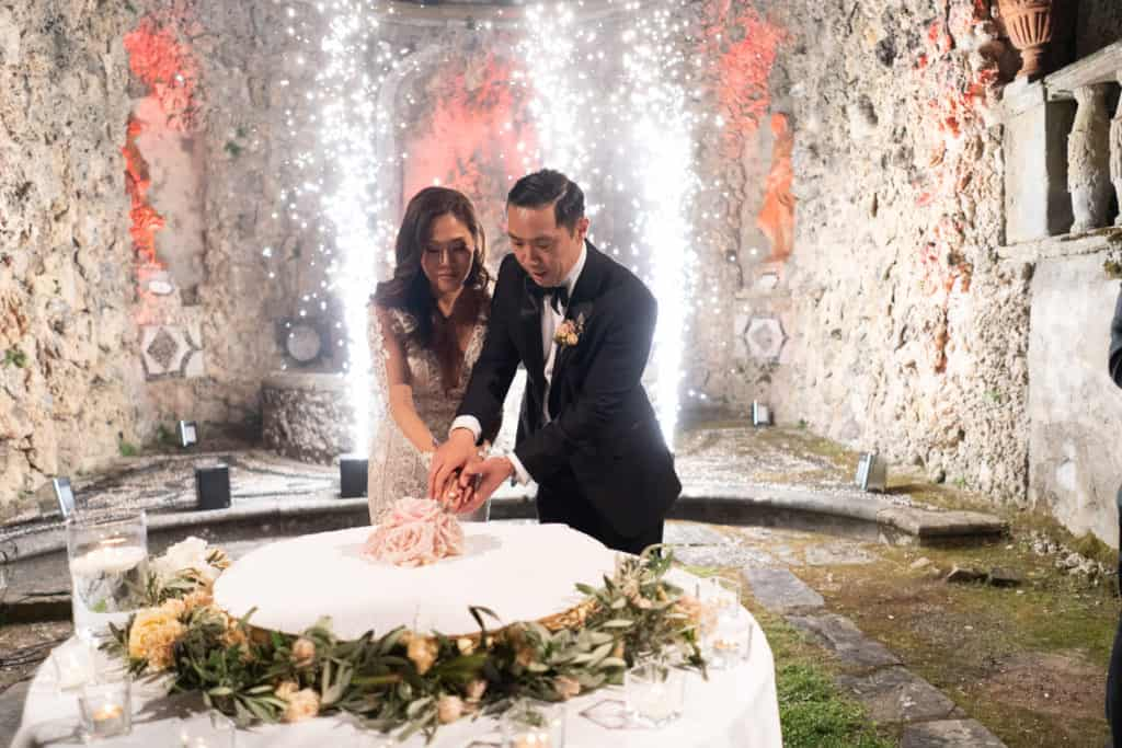 Bride and Groom cutting the wedding cake while having cold fireworks shining