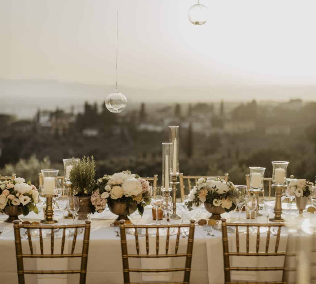 Italian Wedding Planners are set up Wedding table decorated with golden chairs, white candles, flowers and glassed bulbs