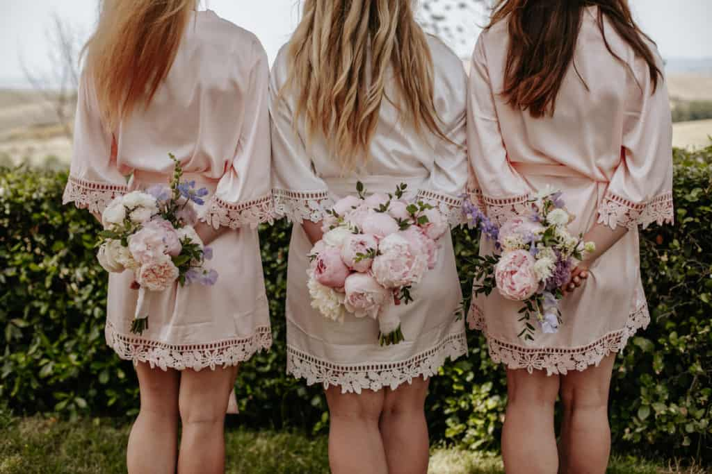 Bride and bridesmaids with bouquet of buttercups and flowers
