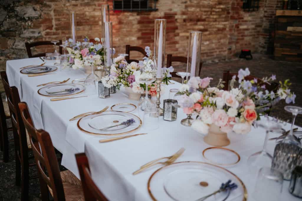 Luxury wedding table setup with lilac candles, flowers and glass underplot