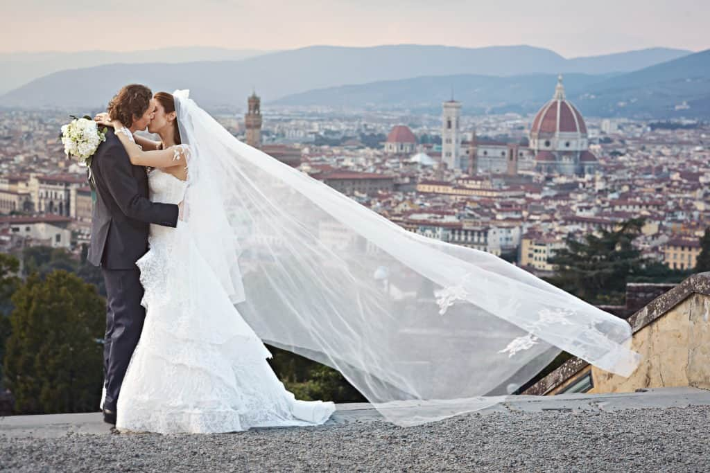 Bride and Groom kissing each other having Florence's Dome as background