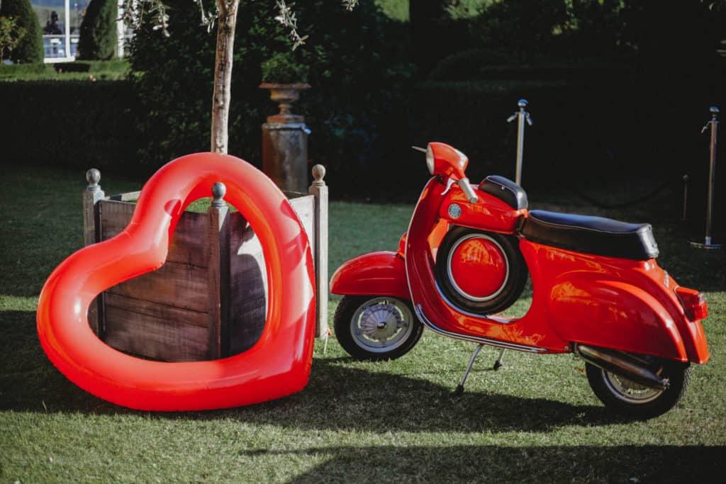 Red Vespa near red heart shaped baloon in wedding garden